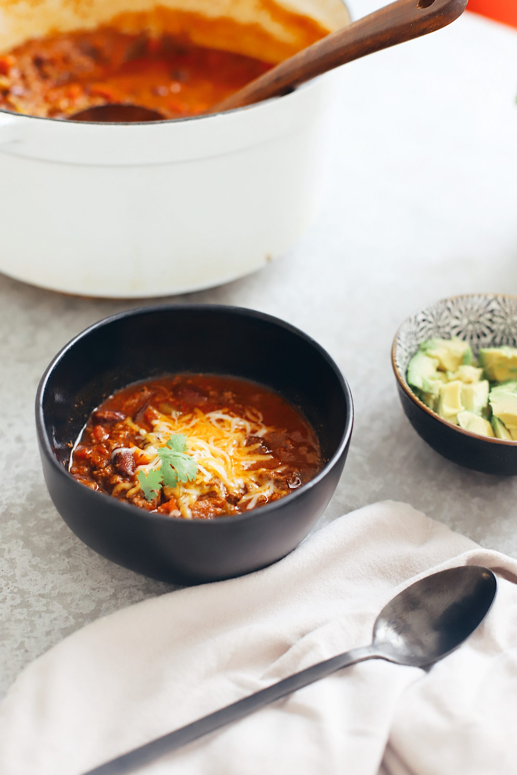 Easy Family Favorite Chili recipe! Make this delicious classic homemade chili in the crockpot or in one pot easily. It's THE BEST CHILI, and my family asks me to make it over and over. | Chili Recipe by popular Florida lifestyle blog, Fresh Mommy Blog: image of chili in a black ceramic bowl with shredded cheese on top.