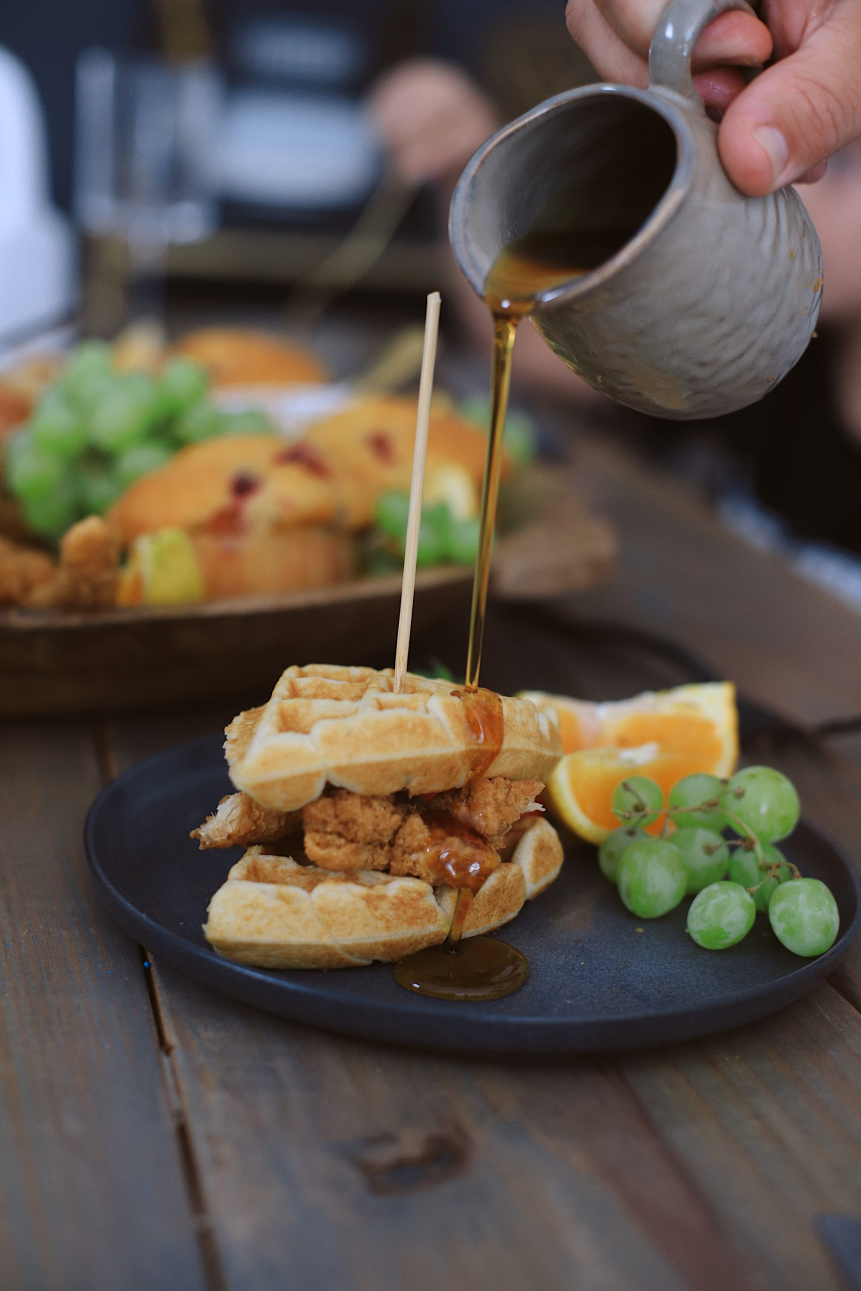 Easy Waffle Recipe for an Amazing Breakfast for Dinner Family Night - Chicken and Waffles Breakfast Board | Waffle Recipe by popular Florida lifestyle blog, Fresh Mommy Blog: image of a person pouring syrup on a chicken and waffle sandwich.