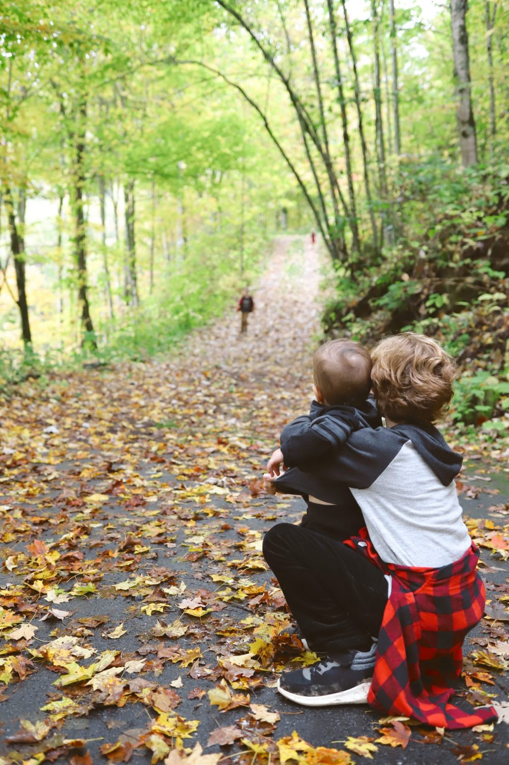Road Trip Packing Tips by popular Florida travel blog, Fresh Mommy Blog: image of a young boy holding his baby brother on a path surrounded by trees and covered with fallen leaves.