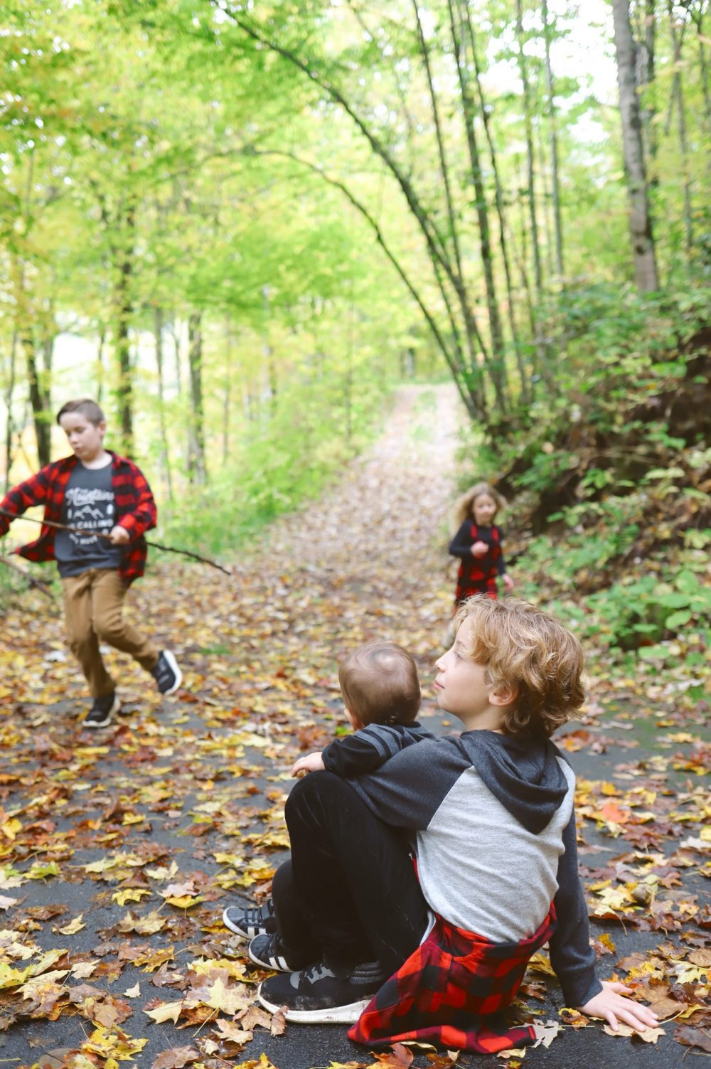 Road Trip Packing Tips by popular Florida travel blog, Fresh Mommy Blog: image of some young girls and boys playing on a path surrounded by trees and covered with fallen leaves.
