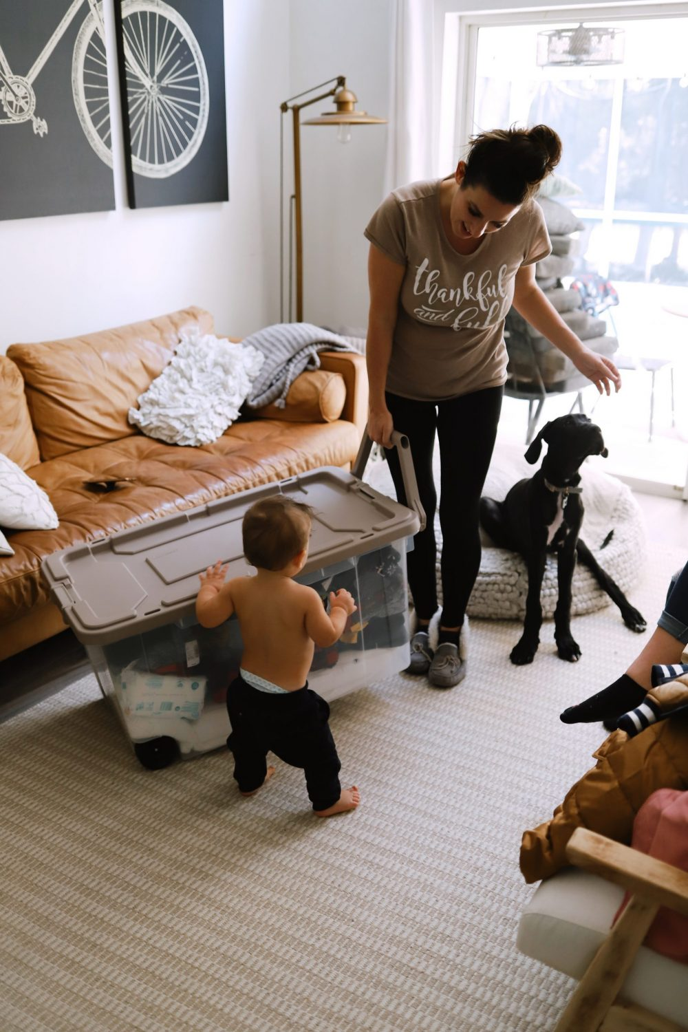 Road Trip Packing Tips by popular Florida travel blog, Fresh Mommy Blog: image of a mom standing in her living room next to her great dane puppy and baby and holding a clear storage container filled with travel gear.