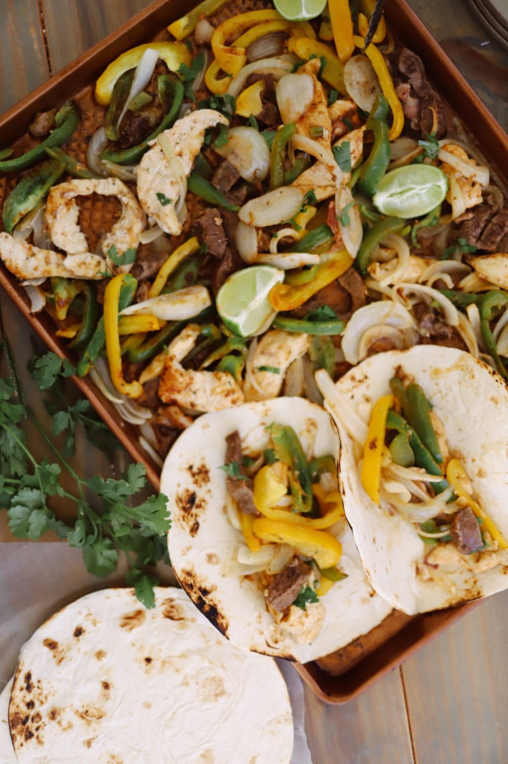 Dinner made easy and ALL IN ONE PAN with these steak and chicken sheet pan fajitas. Set it out on the table and serve with toppings to feed a big family easily!