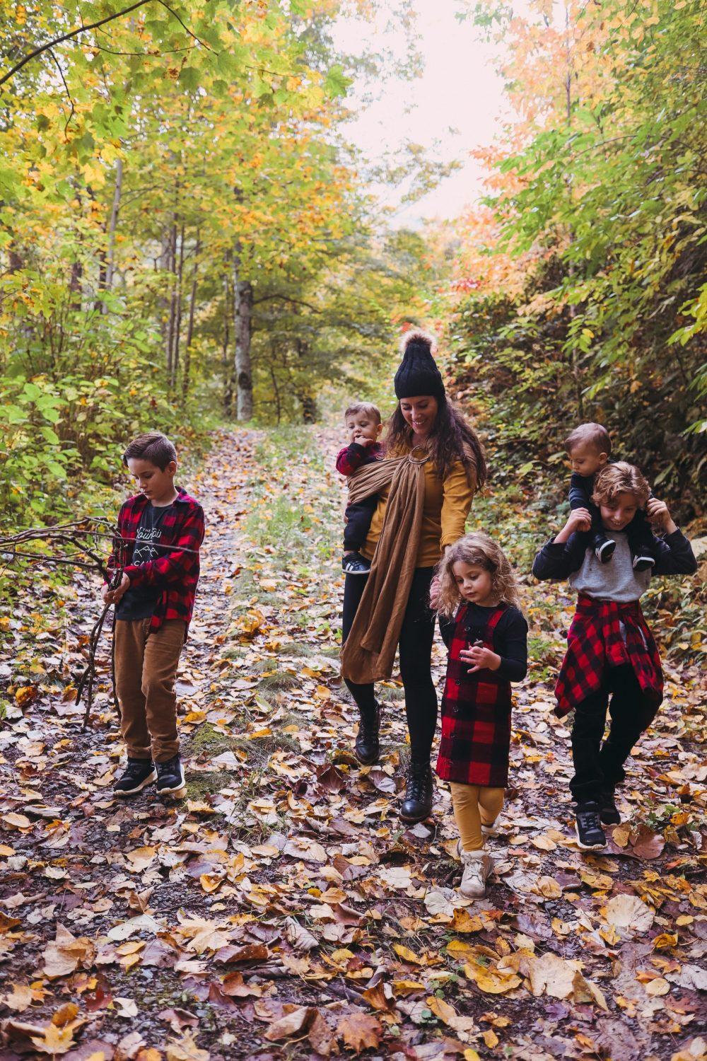 Road Trip Packing Tips by popular Florida travel blog, Fresh Mommy Blog: image of a family standing out on a path covered with fallen leaves.