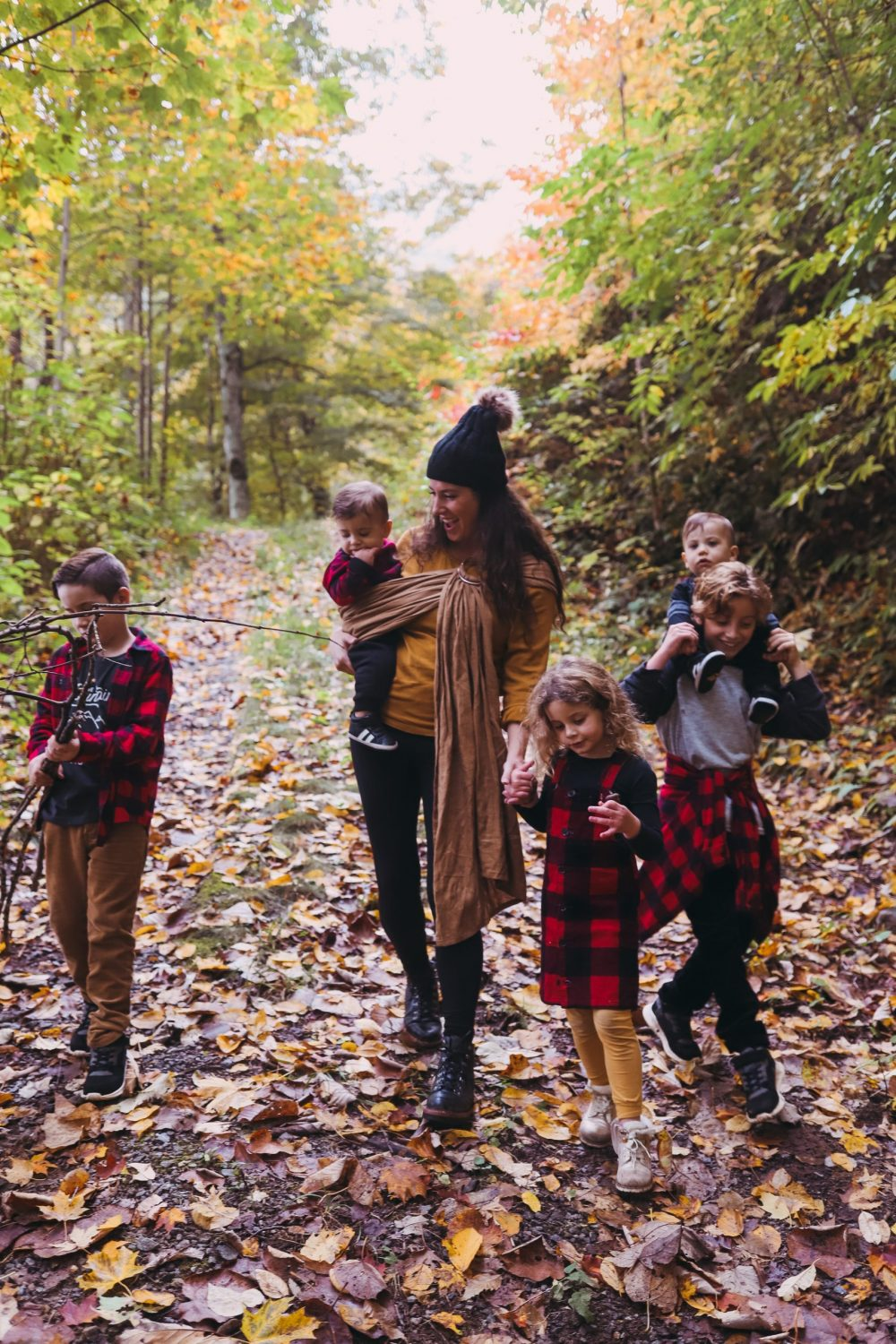 Road Trip Packing Tips by popular Florida travel blog, Fresh Mommy Blog: image of a mom and her young kids standing on a path surrounded by trees and covered with fallen yellow leaves.