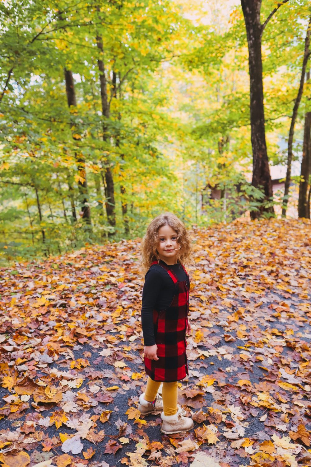 Road Trip Packing Tips by popular Florida travel blog, Fresh Mommy Blog: image of a little girl standing on a path covered with fallen yellow leaves.