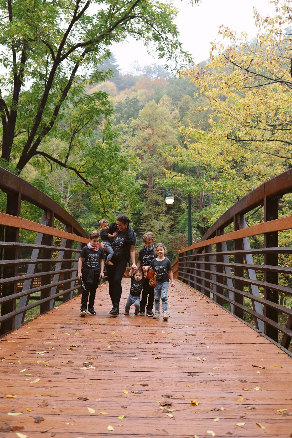 Road Trip Packing Tips by popular Florida travel blog, Fresh Mommy Blog: image of a mom and her young children wearing matching shirts and standing on a bridge surrounded by trees.