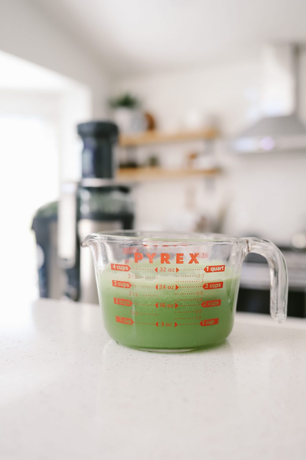 The Best Easy Clean Juicer Review for 2021: We tested easy clean juicers and this is what we found. Easy Clean Juicer by popular Florida lifestyle blog, Fresh Mommy Blog: image of green juice in a glass Pyrex measuring cup.