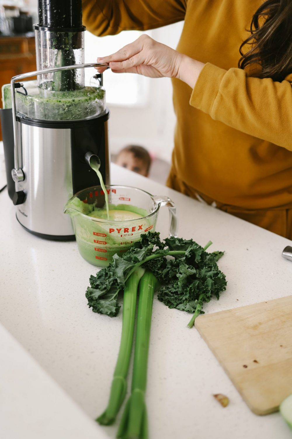 The Best Easy Clean Juicer Review for 2021: We tested easy clean juicers and this is what we found.  Easy Clean Juicer by popular Florida lifestyle blog, Fresh Mommy Blog: image of a woman making green juice in her easy clean juicer.
