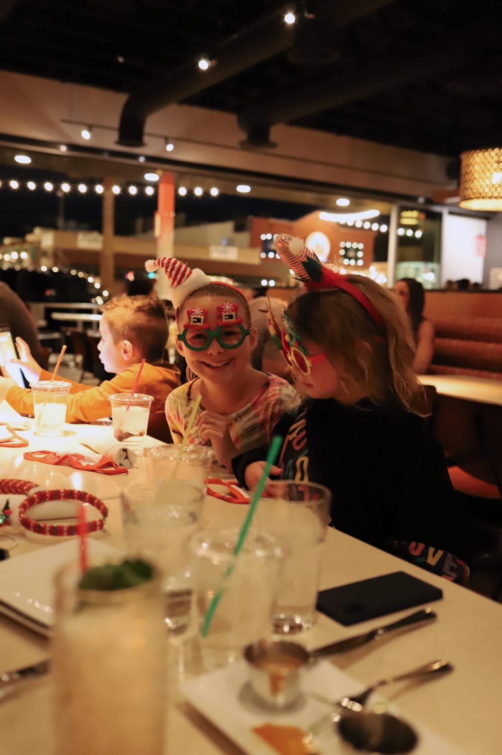 One of the Best Secret Winter Sun Destinations, Scottsdale Arizona. Family-friendly dinner at Hula's Modern Tiki |Guide by popular Florida travel blog, Fresh Mommy Blog: image of two young girls wearing Christmas glasses.