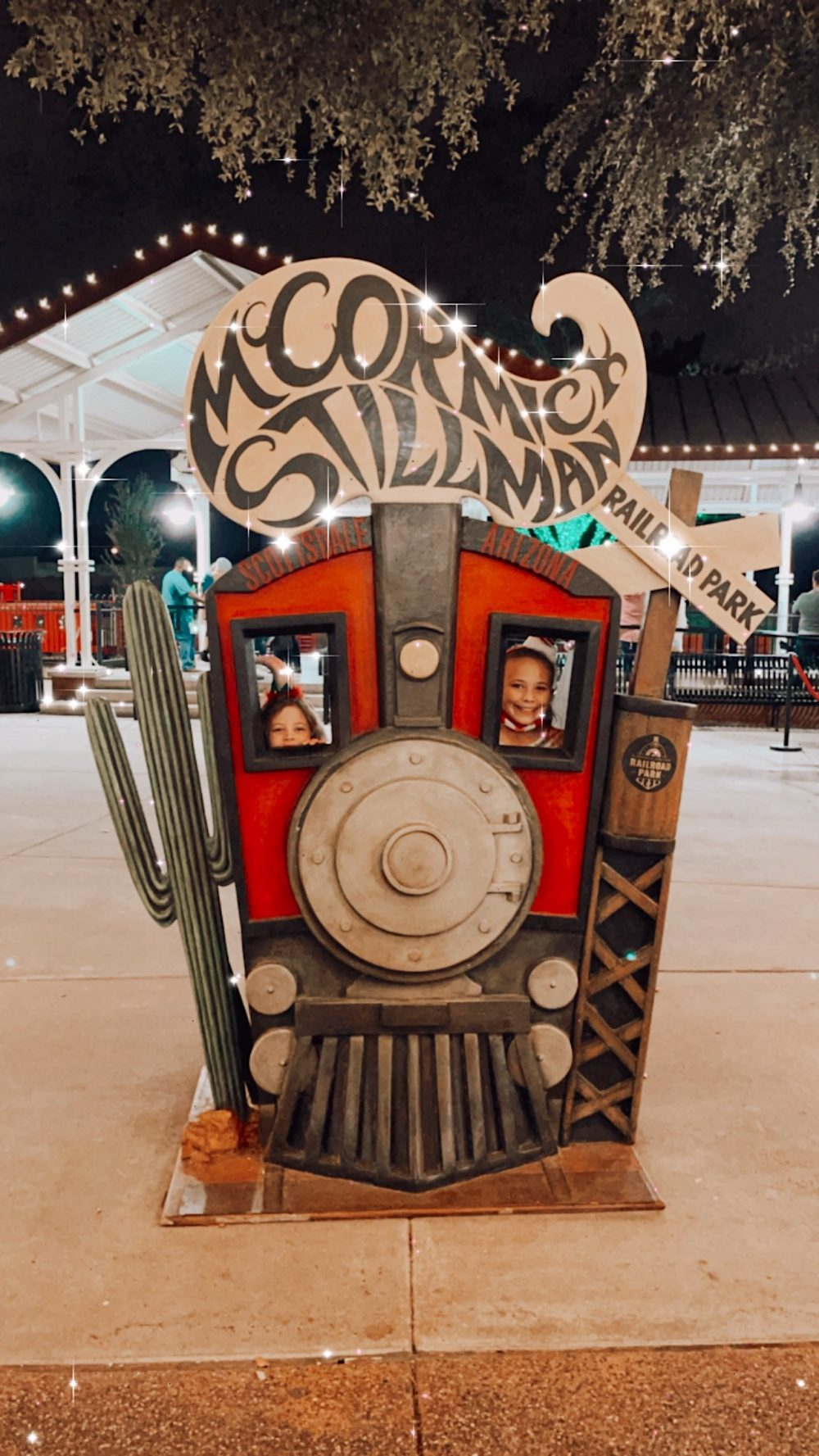 One of the Best Secret Winter Sun Destinations, Scottsdale Arizona. Family-friendly Holiday Lights train at McCormick-Stillman Railroad park |Guide by popular Florida travel blog, Fresh Mommy Blog: image of two girls sticking their faces through a railroad train cutout.