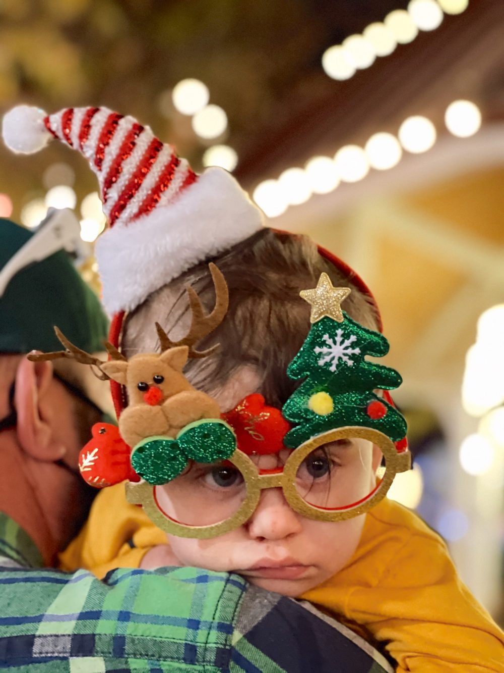 One of the Best Secret Winter Sun Destinations, Scottsdale Arizona. Family-friendly Holiday Lights train at McCormick-Stillman Railroad park |Guide by popular Florida travel blog, Fresh Mommy Blog: image of a baby boy wearing Christmas glasses.