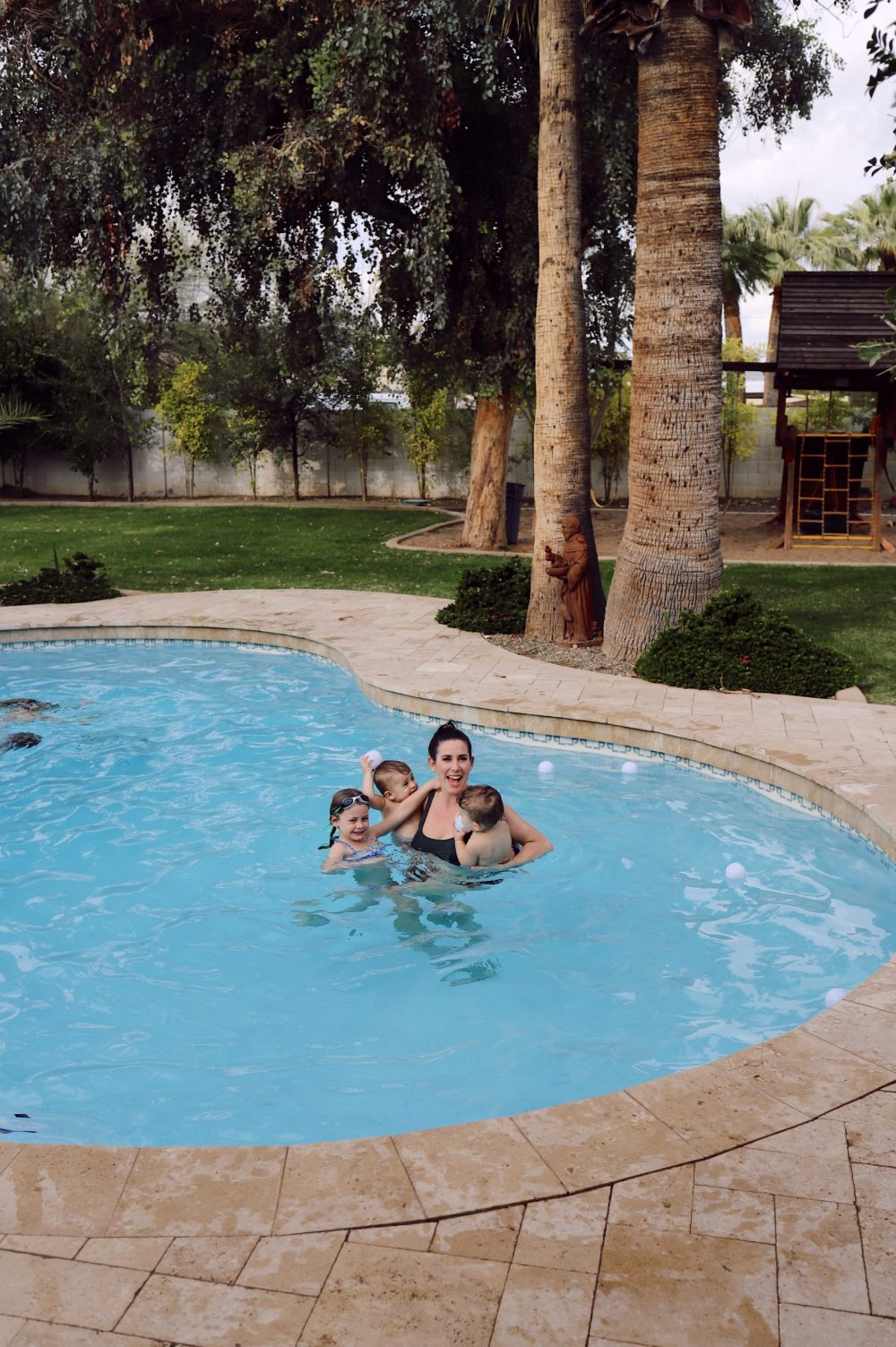 One of the Best Secret Winter Sun Destinations, Scottsdale Arizona. Family-friendly property rental at Bella's Villa Voltaire |Guide by popular Florida travel blog, Fresh Mommy Blog: image of a mom and her babies swimming in a outdoor pool.