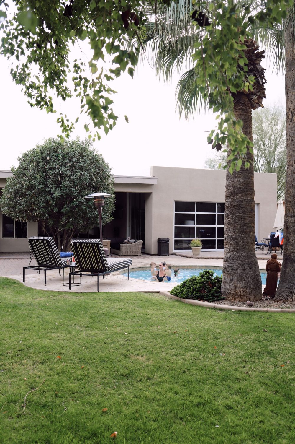One of the Best Secret Winter Sun Destinations, Scottsdale Arizona. Family-friendly property rental at Bella's Villa Voltaire |Guide by popular Florida travel blog, Fresh Mommy Blog: image of a mom and her babies swimming in a outdoor pool at Bella's Villa Voltaire.