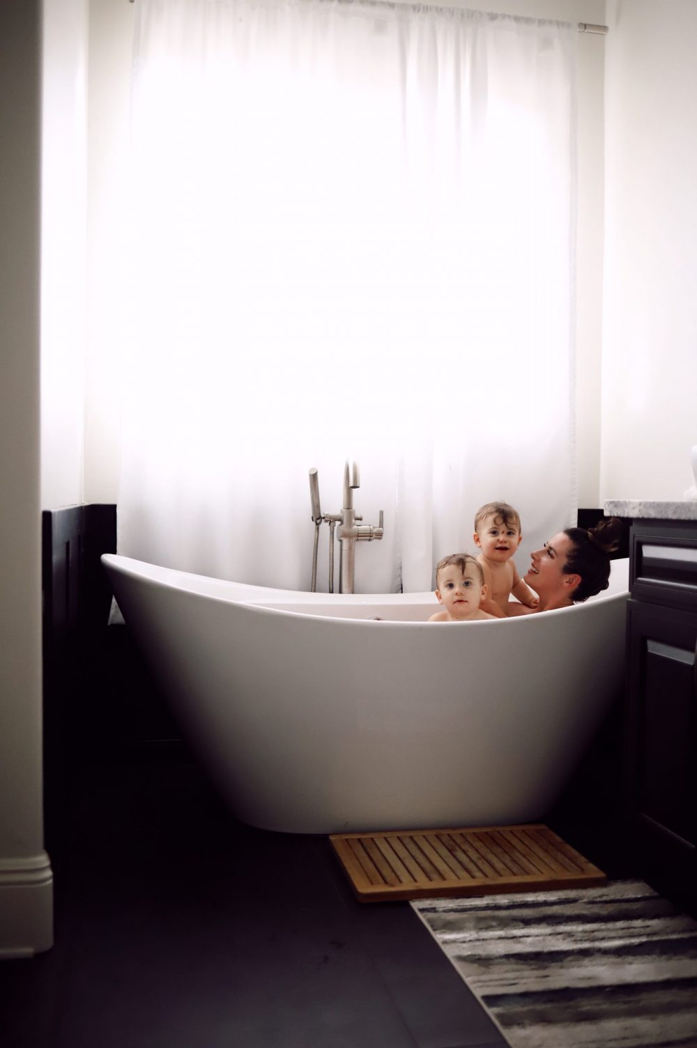 One of the Best Secret Winter Sun Destinations, Scottsdale Arizona. Family-friendly property rental at Bella's Villa Voltaire |Guide by popular Florida travel blog, Fresh Mommy Blog: image of a mom and her babies sitting in a soaking tub at Bella's Villa Voltaire.