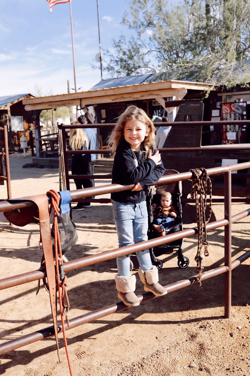 One of the Best Secret Winter Sun Destinations, Scottsdale Arizona. Horseback riding in the desert and family-friendly activities at MacDonald's Ranch. |Guide by popular Florida travel blog, Fresh Mommy Blog: image of a little girl standing on a metal fence.