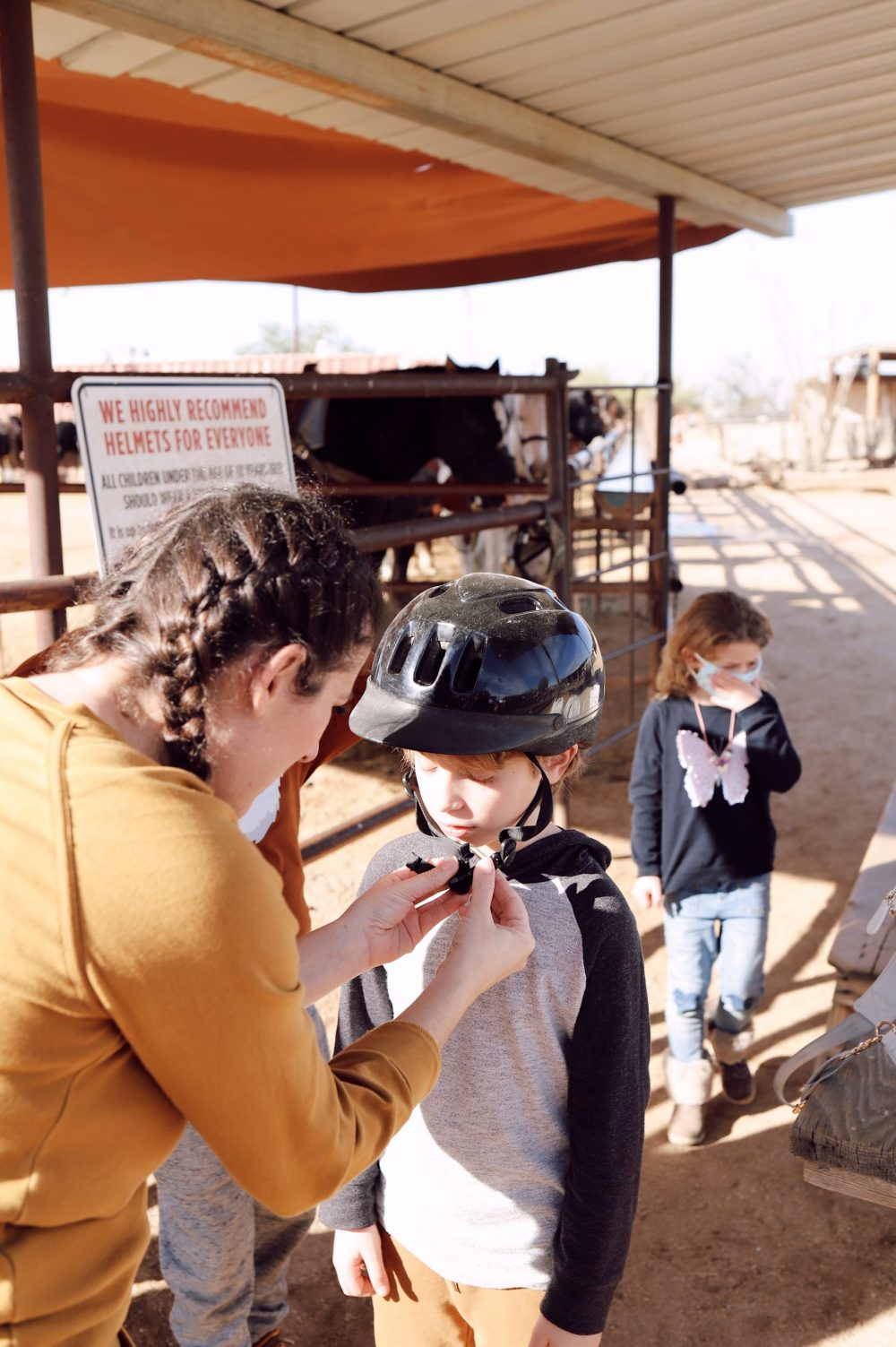 One of the Best Secret Winter Sun Destinations, Scottsdale Arizona. Horseback riding in the desert and family-friendly activities at MacDonald's Ranch. |Guide by popular Florida travel blog, Fresh Mommy Blog: image of a mom buckling a black helmet on her son's head.