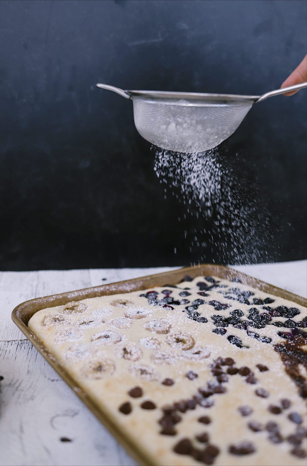 Amazingly Easy Sheet Pan Pancakes With Buttermilk Pancake Mix. Family breakfast ideas with 37 pancake add-in ideas. Big batch breakfast with baked pancakes to feed a crowd. |Krusteaz Buttermilk Pancake Mix by popular Florida lifestyle blog, Fresh Mommy: image of a woman sprinkling powders sugar on sheet pan pancakes.