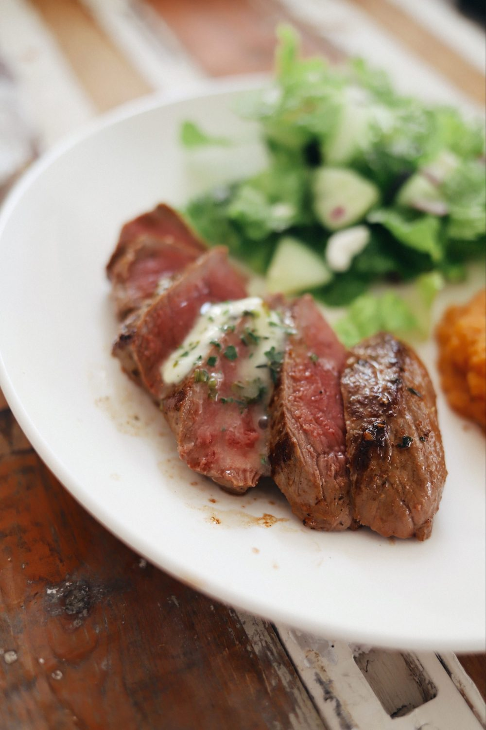 Homemade Steak Butter: How to Make an Easy Steakhouse Herb Butter for Steak  Steak Butter by popular Florida lifestyle blog, Fresh Mommy Blog: image of slices pieces of steak with melted steak butter on top.