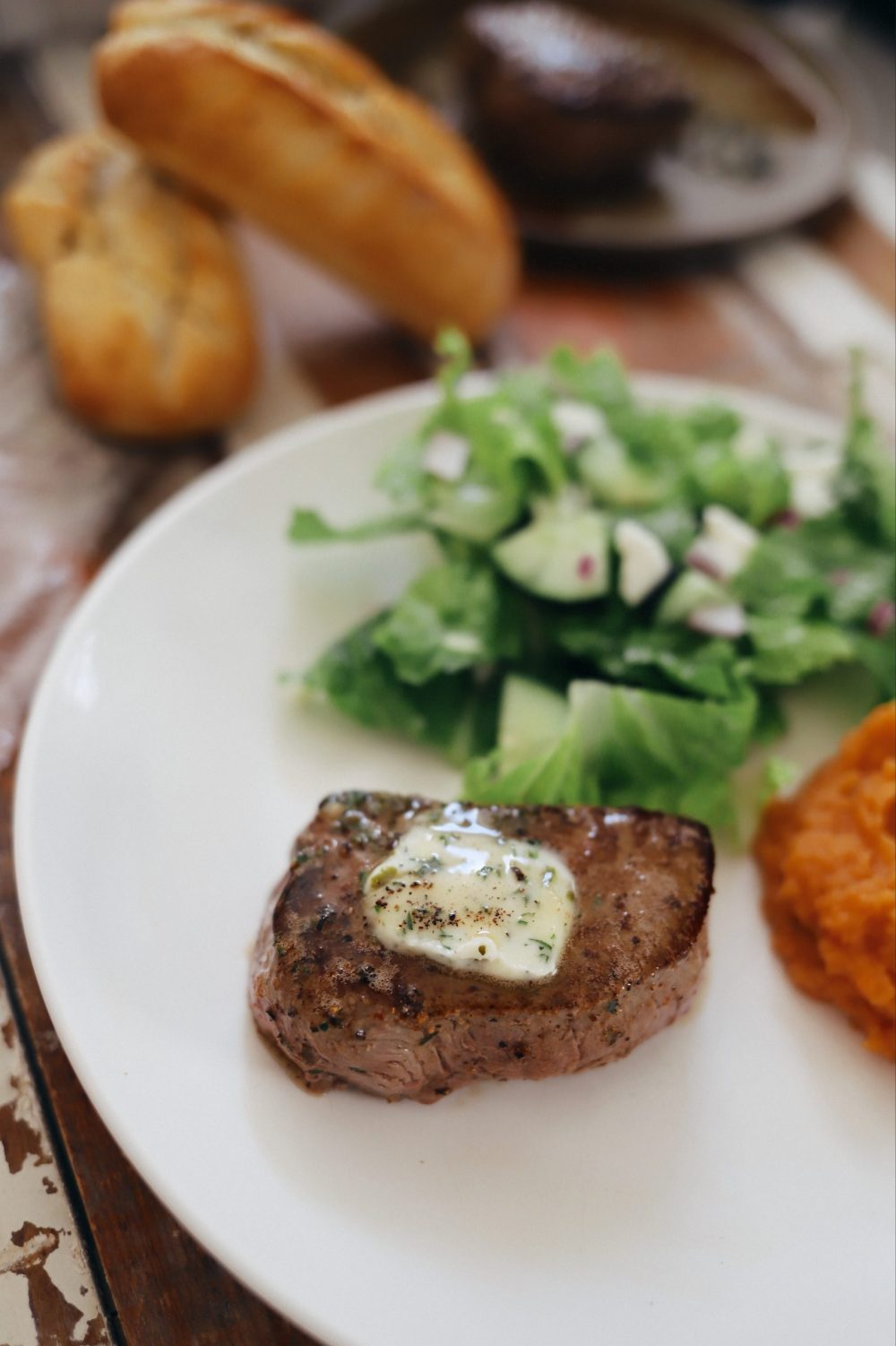 Homemade Steak Butter: How to Make an Easy Steakhouse Herb Butter for Steak  Steak Butter by popular Florida lifestyle blog, Fresh Mommy Blog: image of a piece of steak on a white plate with some herb butter on top of it.