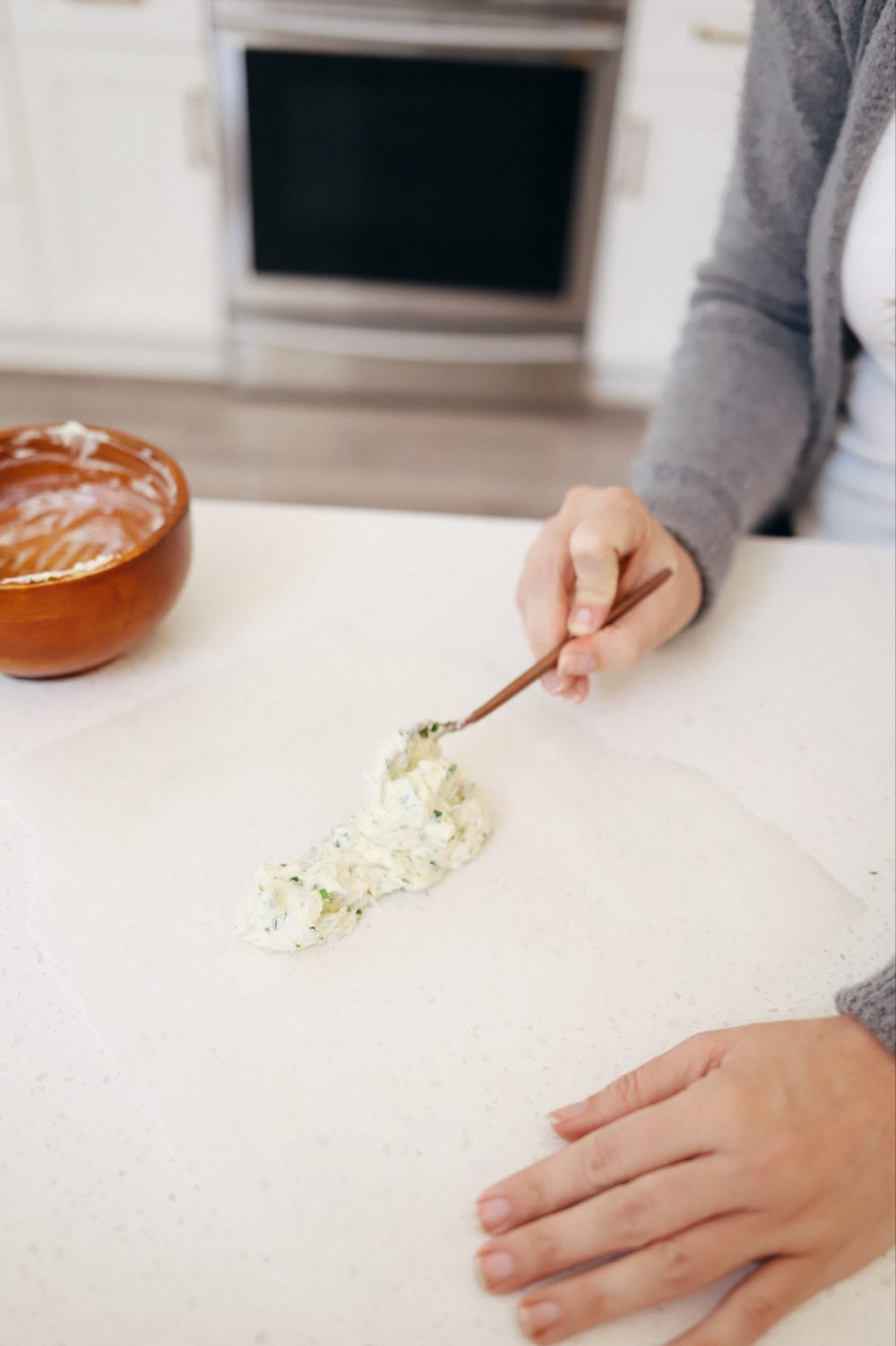 Homemade Steak Butter: How to Make an Easy Steakhouse Herb Butter for Steak  Steak Butter by popular Florida lifestyle blog, Fresh Mommy Blog: image of a woman spreading butter on some wax paper.