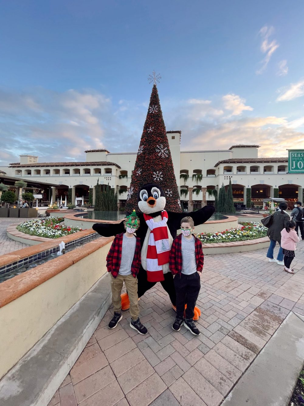 One of the Best Year Round Sun Destinations for Large Family Friendly Travel, Scottsdale Arizona. Holiday Winter Fun at Christmas at the Princess at the Fairmont Scottsdale Princess. |Guide by popular Florida travel blog, Fresh Mommy Blog: image of two young boys standing with someone in a penguin costume.