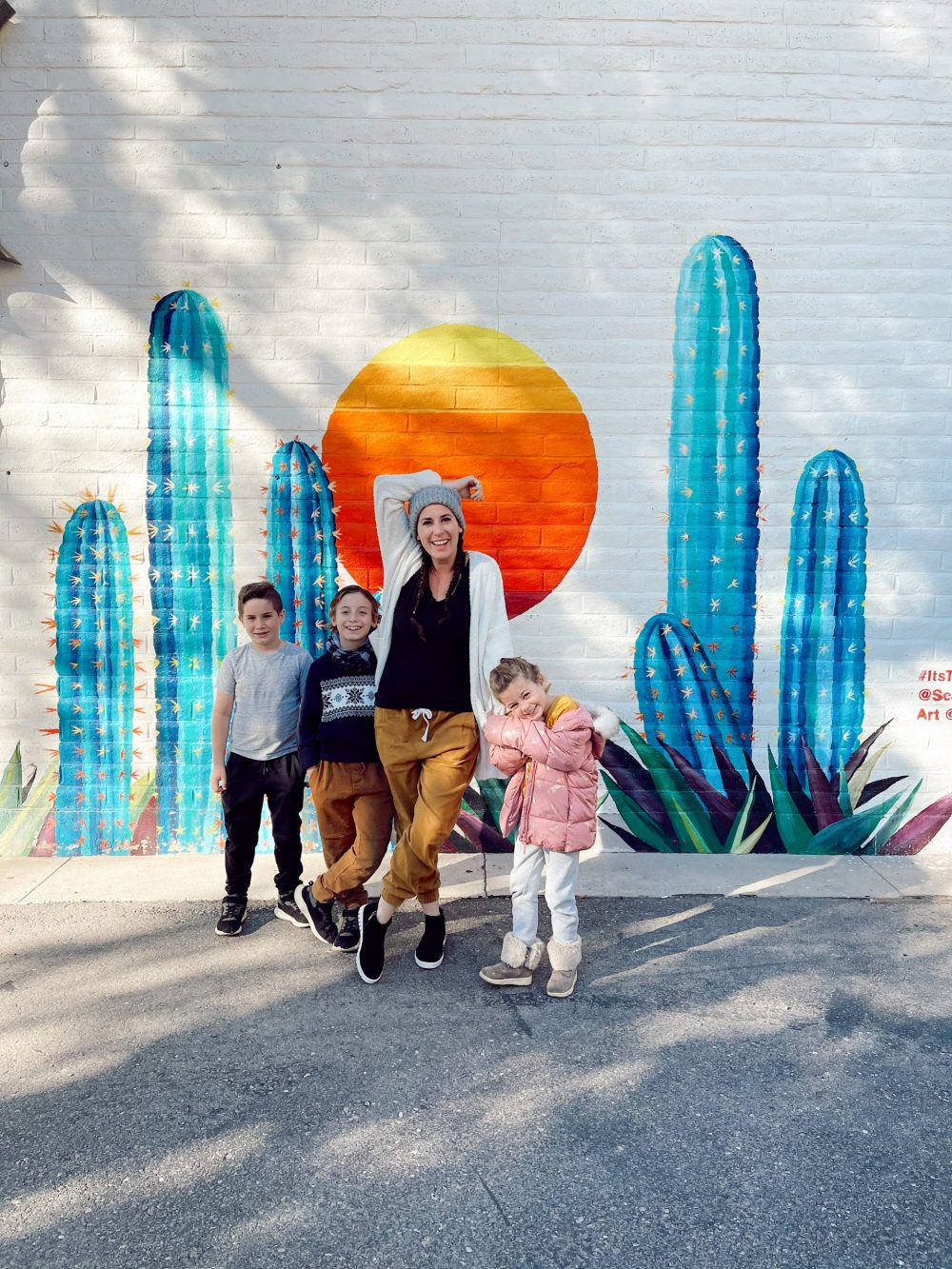 One of the Best Year Round Sun Destinations for Large Family Friendly Travel, Scottsdale Arizona |Guide by popular Florida travel blog, Fresh Mommy Blog: image of a mom and her kids standing in front of a cactus wall mural.