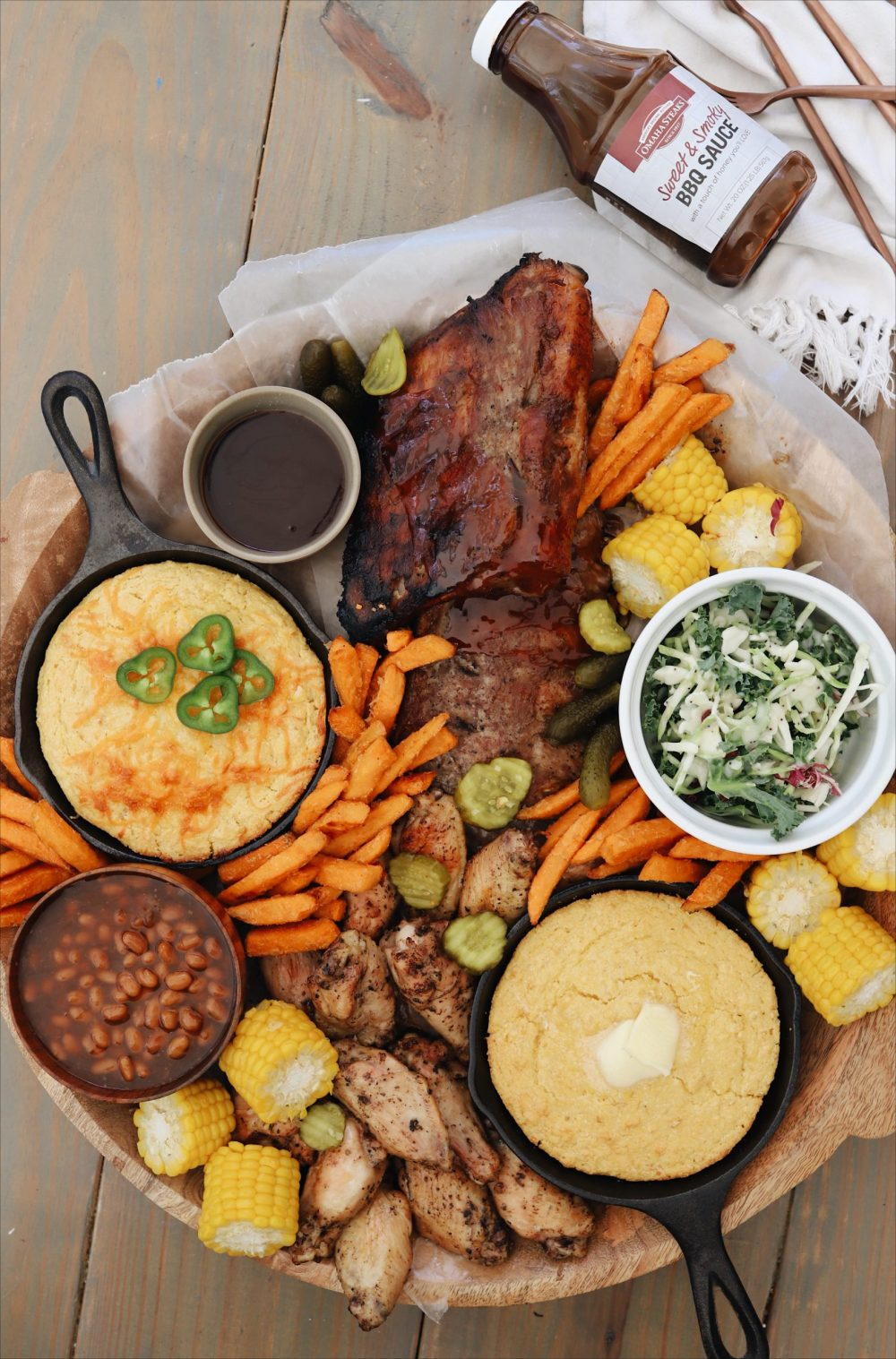 The Easiest Slow Cooker Ribs Recipe You Will Ever Make for tender fall off the bone ribs! |Slow Cooker Ribs by popular Florida lifestyle blog, Fresh Mommy Blog: image of slow cooker ribs on a wooden tray with sweet potato fries, corn on the cob, skillet corn bread, chicken wings, and a white ceramic dish of coleslaw.