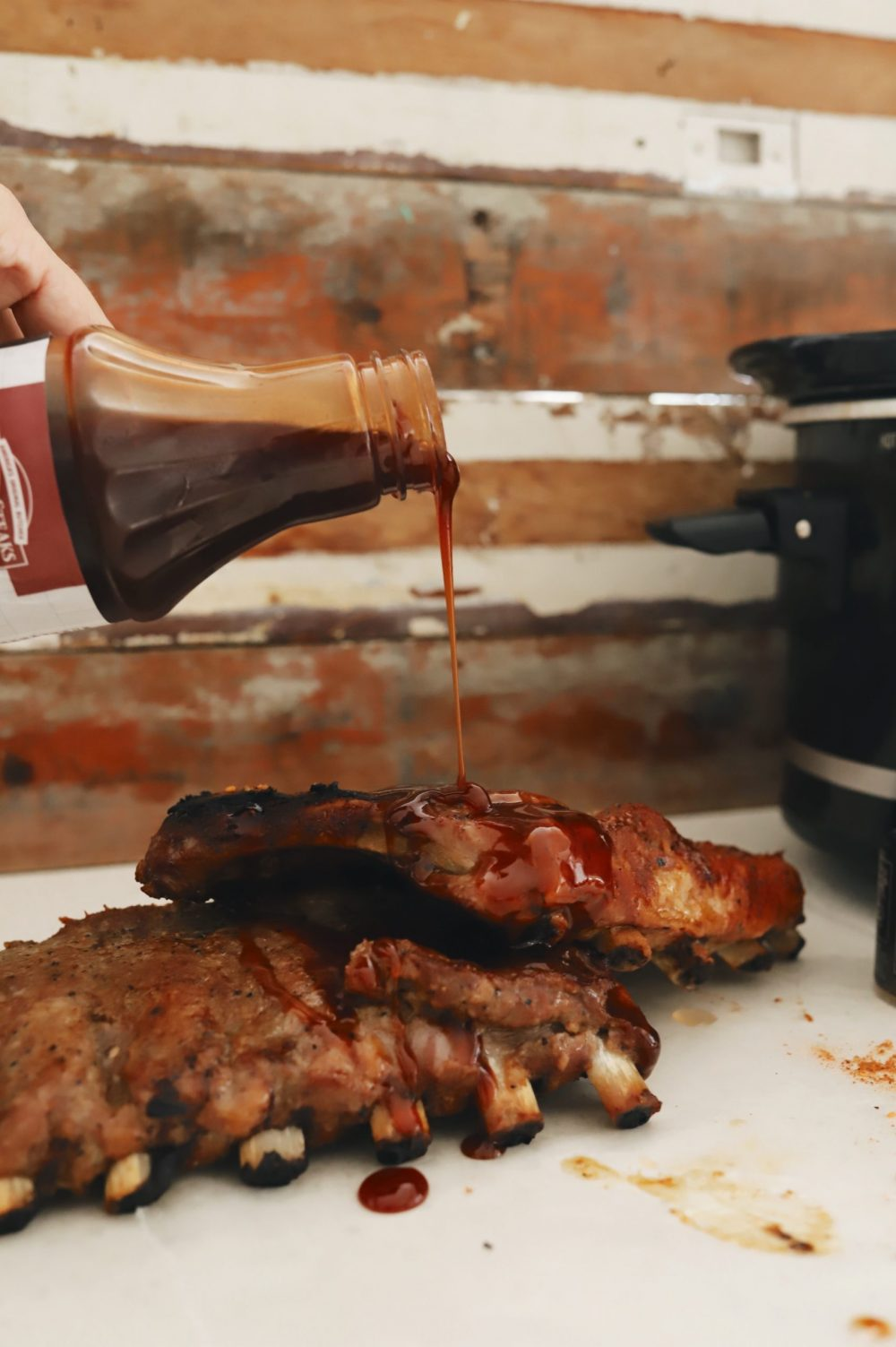 The Easiest Slow Cooker Ribs Recipe You Will Ever Make for tender fall off the bone ribs! |Slow Cooker Ribs by popular Florida lifestyle blog, Fresh Mommy Blog: image of someone pouring BBQ sauce on some slow cooker ribs.