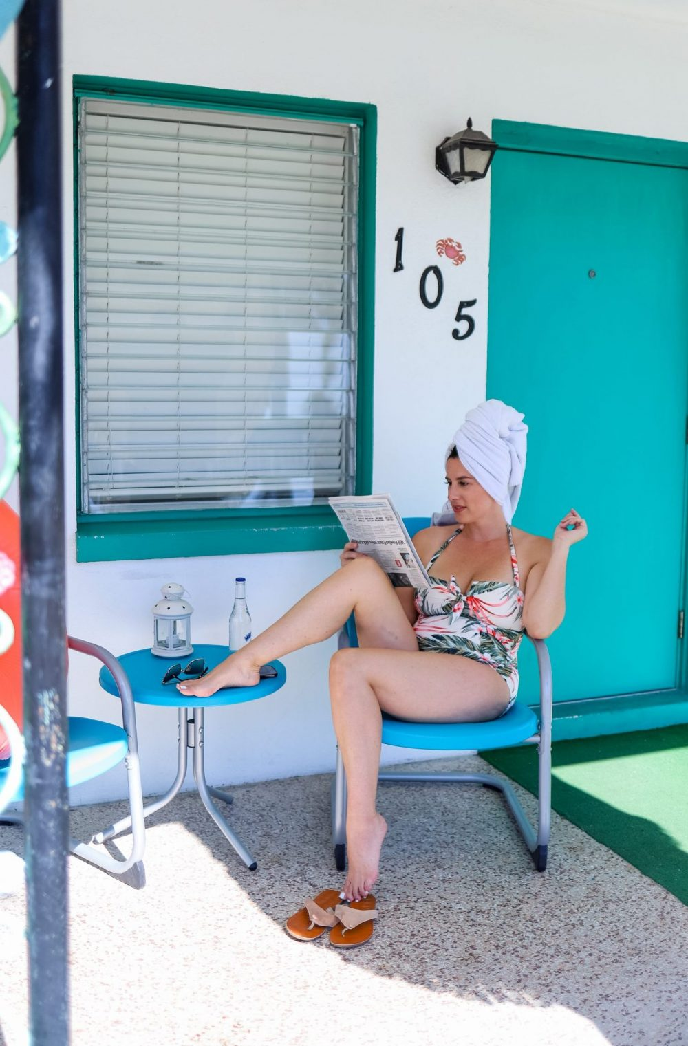 Style on a Budget: 9 Best Swimsuits for Moms  Swimsuits for Moms by popular Florida fashion blog, Fresh Mommy Blog: image of a woman sitting outside her Palm Court motel room and wearing a tropical print one piece halter swimsuit.