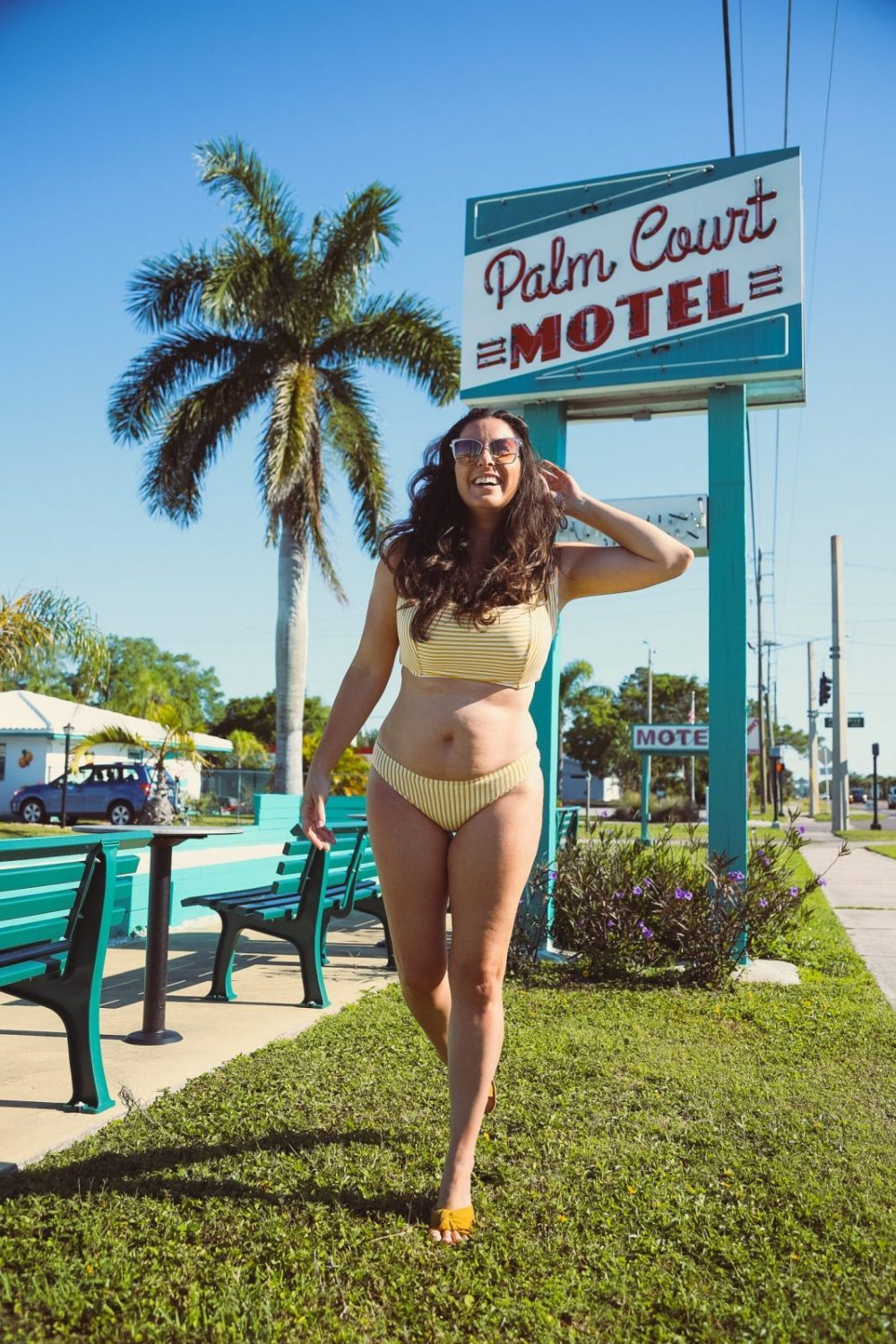 Style on a Budget: 9 Best Swimsuits for Moms   Swimsuits for Moms by popular Florida fashion blog, Fresh Mommy Blog: image of a woman standing outside at the Palm Court Motel and wearing a yellow stripe two piece swimsuit.
