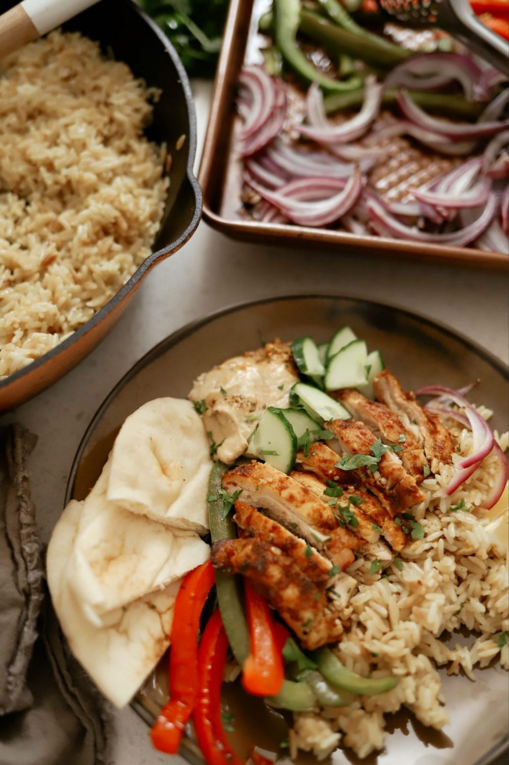 Sheet Pan Chicken Shawarma with Rice Recipe featured by top FL lifestyle blogger, Tabitha Blue of Fresh Mommy Blog   Sheet Pan Chicken Shawarma by popular Florida lifestyle blog, Fresh Mommy Blog: image of sheet pan chicken shawarma on a plate with rice, cucumbers, and pita bread