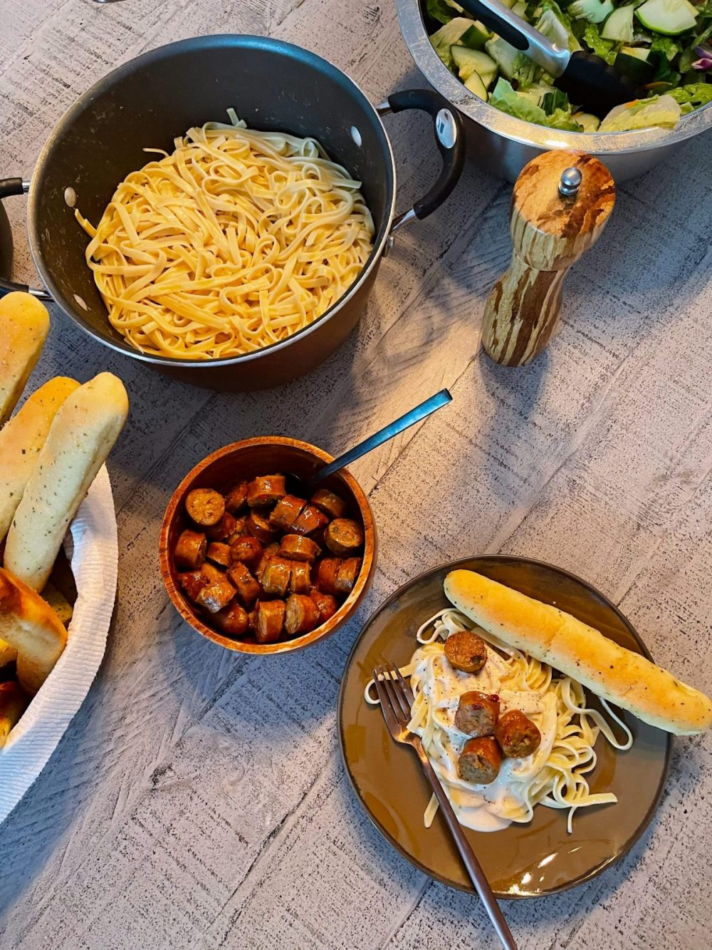 Omaha Steaks Meals featured by top FL lifestyle blogger, Tabitha Blue of Fresh Mommy Blog. - Italian Sausage Alfredo   Omaha Steaks Meals by popular Florida lifestyle blog, Fresh Mommy Blog: image of cut up sausage next to fettuccine noodles and a bowl of salad.
