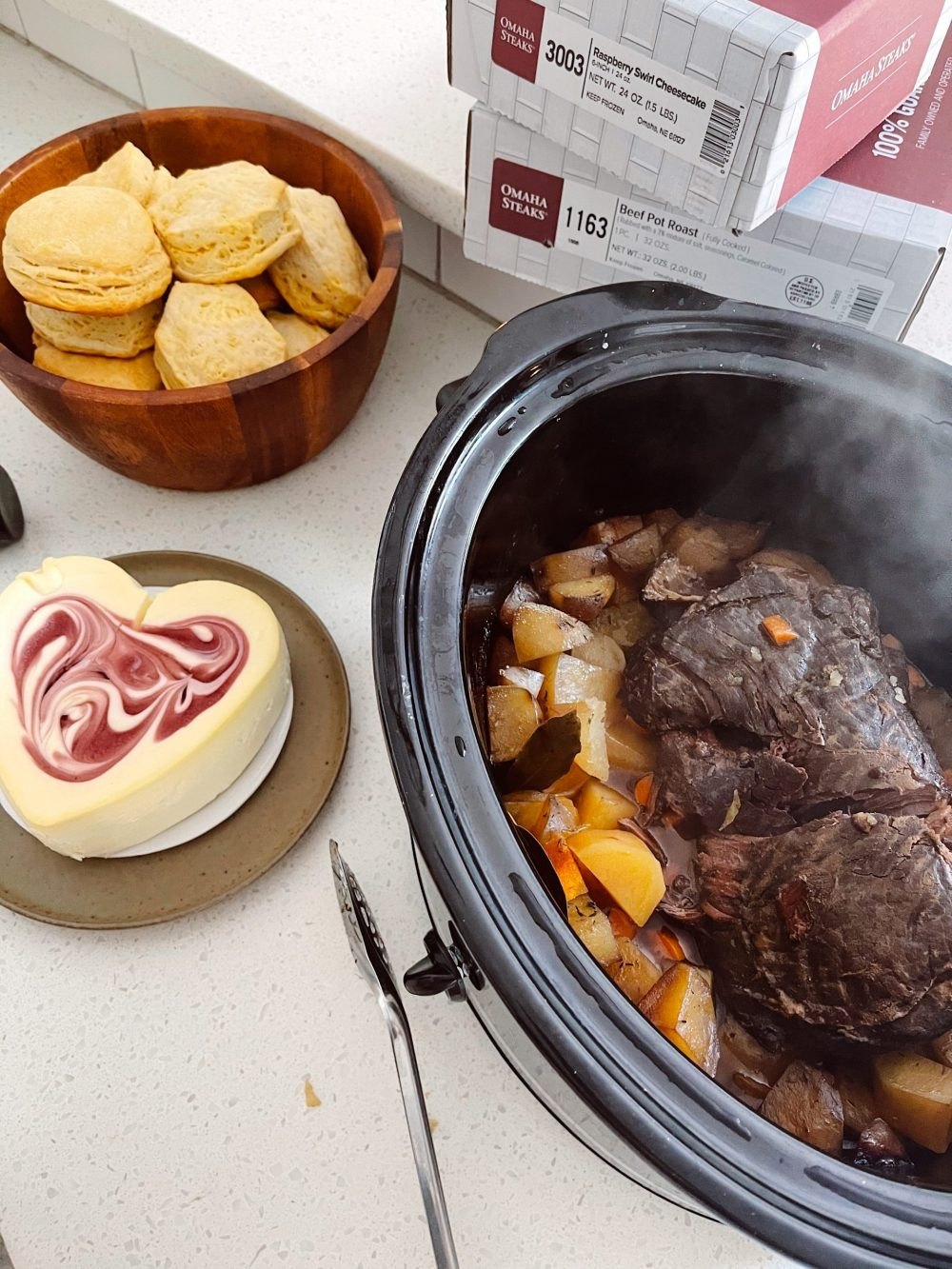 Omaha Steaks Meals featured by top FL lifestyle blogger, Tabitha Blue of Fresh Mommy Blog. - Pot Roast   Omaha Steaks Meals by popular Florida lifestyle blog, Fresh Mommy Blog: image of slow cooker pot roast next to a wooden bowl filled with biscuits and a heart shaped cheese cake.