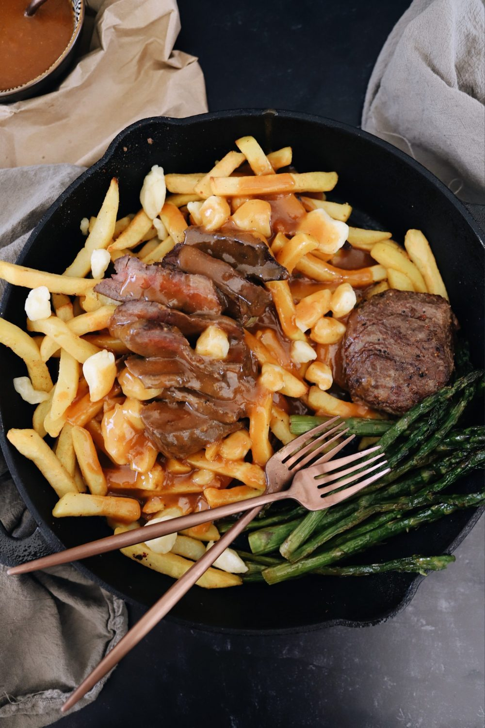 An Easy Steak Poutine Recipe with Fries and Gravy  Poutine Recipe by popular Florida lifestyle blog, Fresh Mommy Blog: image of steak poutine and asparagus in a black skillet.