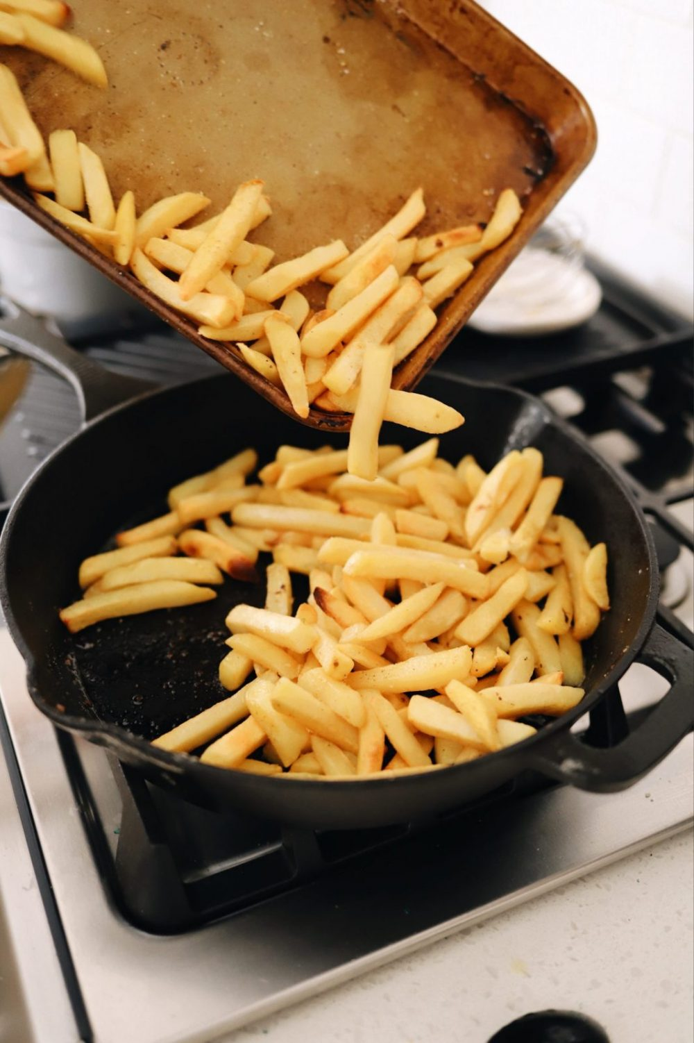 An Easy Steak Poutine Recipe with Fries and Gravy  Poutine Recipe by popular Florida lifestyle blog, Fresh Mommy Blog: image of fries being dumped into a skillet.