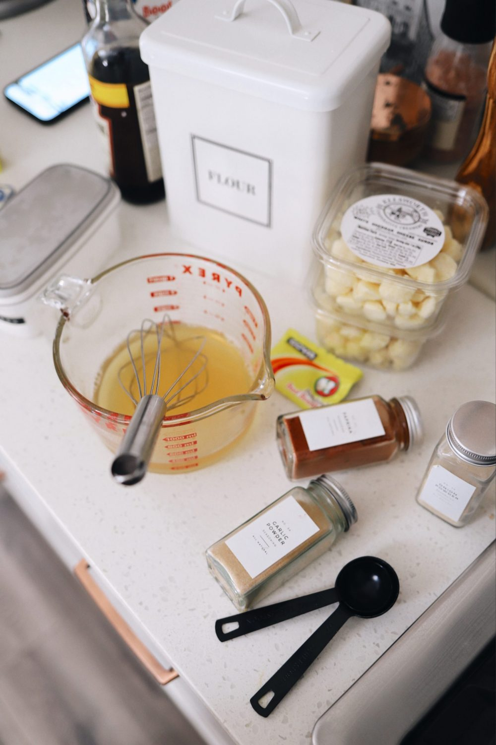An Easy Steak Poutine Recipe with Fries and Gravy  Poutine Recipe by popular Florida lifestyle blog, Fresh Mommy Blog: image of spice jars, chicken stock in a pyrex glass measuring cup, and cheese curds.