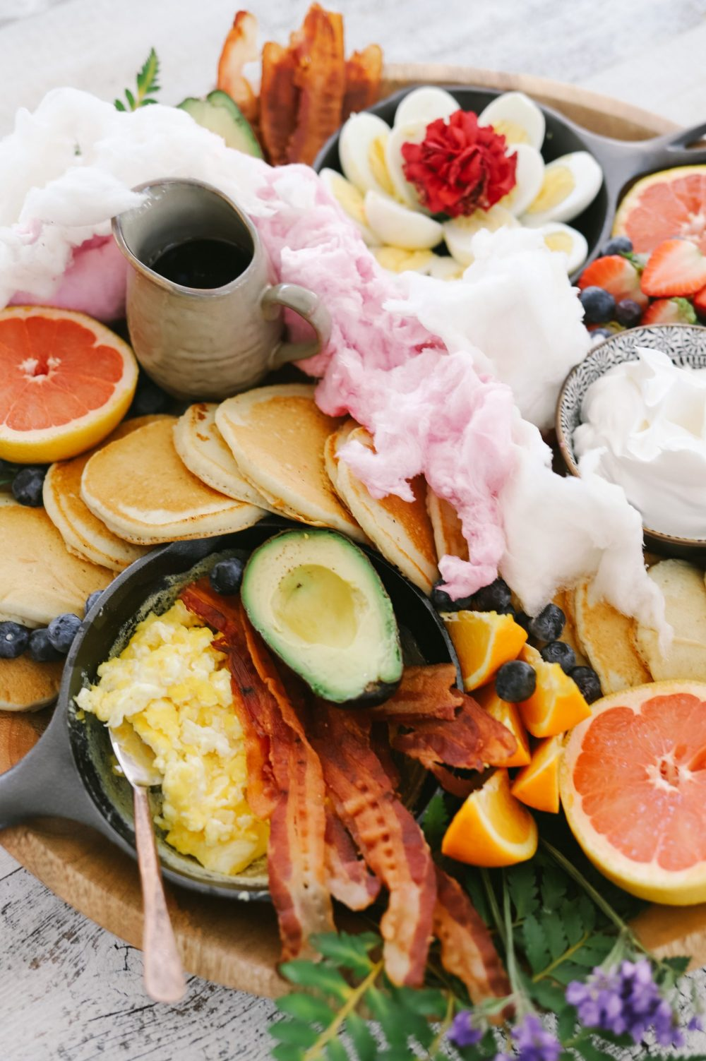 How to Make a Pancake Board That Looks as Delicious as It Tastes. The best Spring Breakfast Board |Pancake Board by popular Florida lifestyle blog, Fresh Mommy Blog: image of a pancake board with pancakes, grapefruit, blueberries, avocado, deviled eggs, bacon, scrambled eggs, and strawberries.