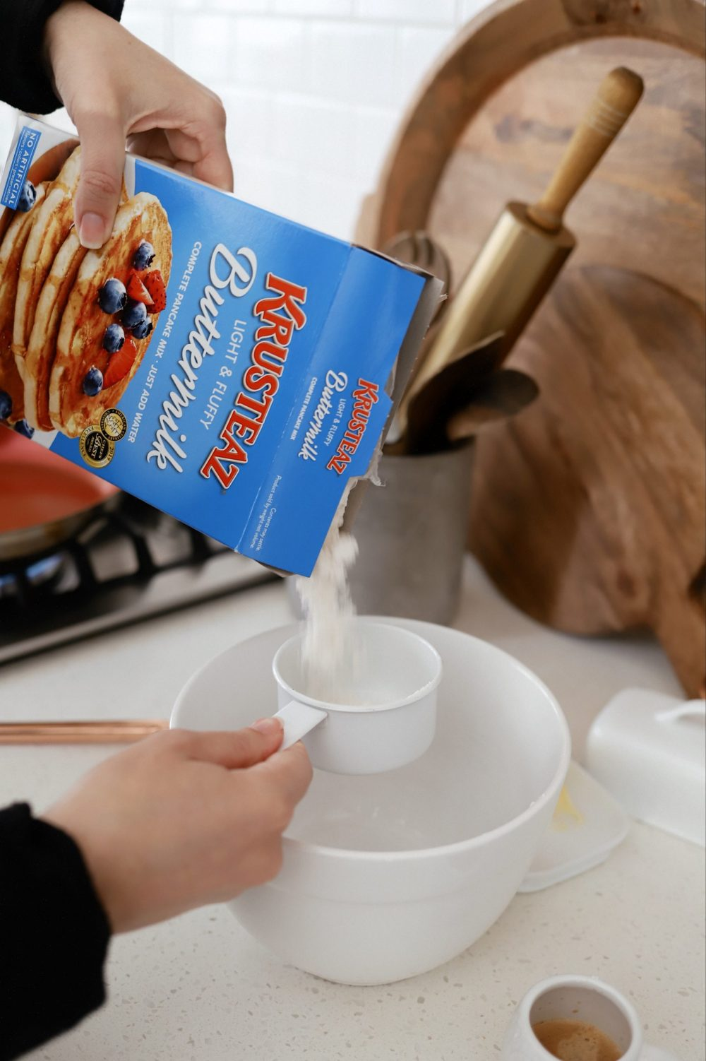 Mouthwatering Coffee Pancakes With Espresso and Vanilla Cream Whip | Coffee Pancakes by popular Florida lifestyle blog, Fresh Mommy Blog: image of a woman pouring Krusteaz buttermilk pancake mix into white measuring cup being held over a white ceramic bowl.