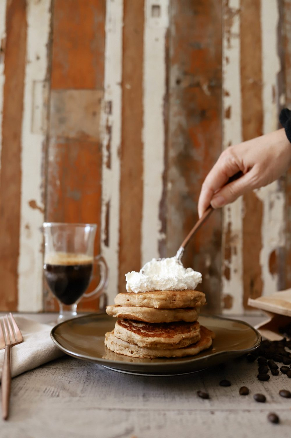 Mouthwatering Coffee Pancakes With Espresso and Vanilla Cream Whip | Coffee Pancakes by popular Florida lifestyle blog, Fresh Mommy Blog: image of a woman topping some stacked coffee pancakes with some espresso whipped cream.