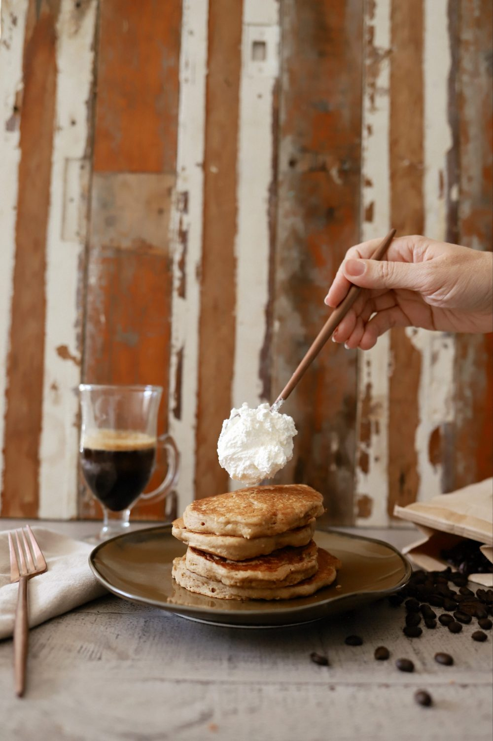Mouthwatering Coffee Pancakes With Espresso and Vanilla Cream Whip | Coffee Pancakes by popular Florida lifestyle blog, Fresh Mommy Blog: image of whipped cream being placed on top of some stacked coffee pancakes.