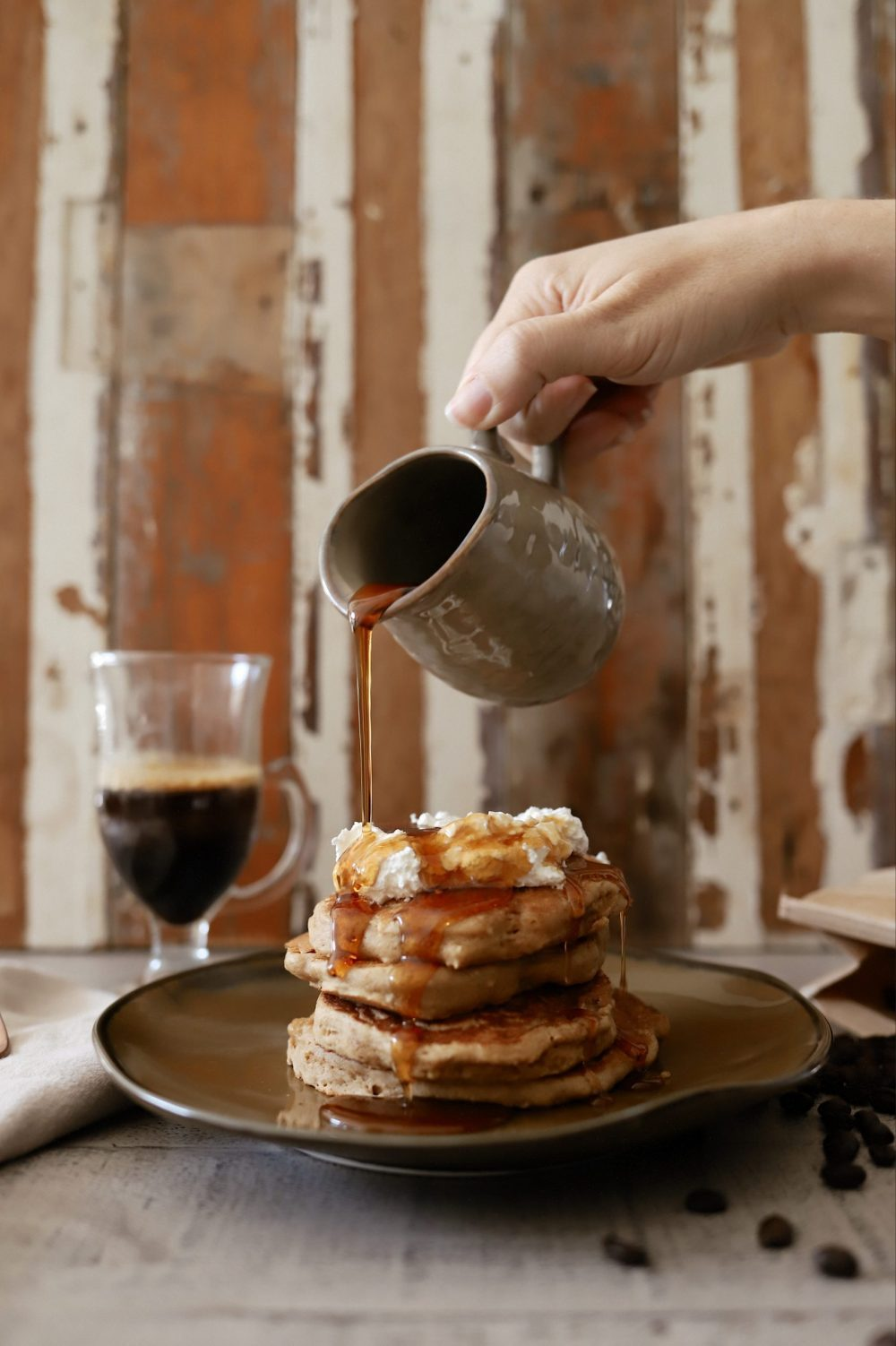 Mouthwatering Coffee Pancakes With Espresso and Vanilla Cream Whip | Coffee Pancakes by popular Florida lifestyle blog, Fresh Mommy Blog: image of some syrup being poured onto stacked pancakes.
