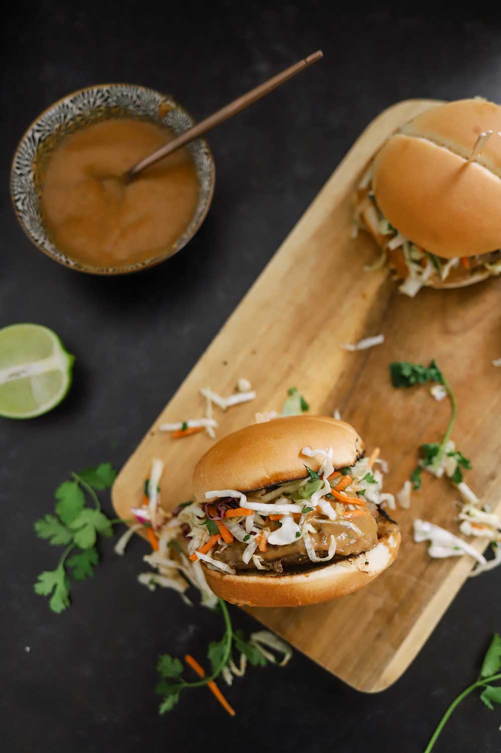 Thai Burgers With Peanut Sauce and 5 Barbeque Side Ideas for delicious family BBQ dinner ideas from top Florida lifestyle and food blogger Tabitha Blue of Fresh Mommy Blog | Thai Burgers by popular Florida lifestyle blog, Fresh Mommy Blog: image of Thai Burgers on a wooden serving board.