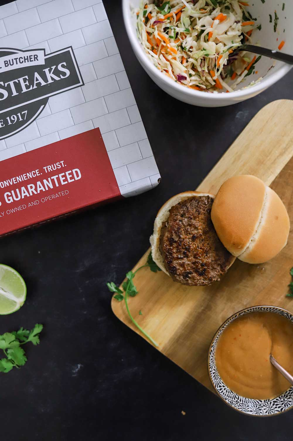 Thai Burgers With Peanut Sauce and 5 Barbeque Side Ideas for delicious family BBQ dinner ideas from top Florida lifestyle and food blogger Tabitha Blue of Fresh Mommy Blog | Thai Burgers by popular Florida lifestyle blog, Fresh Mommy Blog: image of a Thai Burger on a wooden serving board next to a bowl of spice peanut sauce and a Omaha Steaks box.