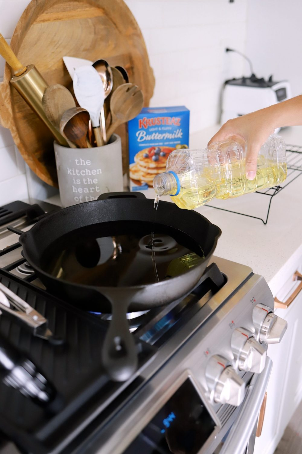 How to Make Yummy Funnel Cake From Pancake Mix at Home   Pancake Mix Funnel Cake, by popular Florida lifestyle blog, Fresh Mommy Blog: image of a woman pouring oil into a skillet.