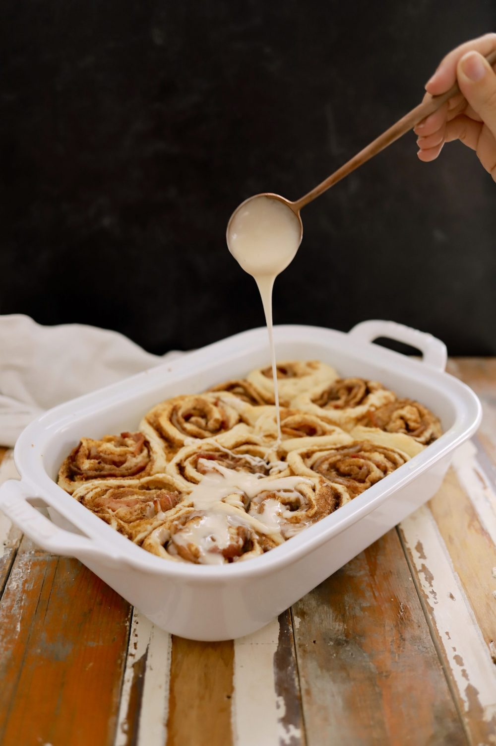 Deliciously Salty Sweet Bacon Cinnamon Rolls with Bourbon Glaze from food and lifestyle blogger Tabitha Blue of Fresh Mommy Blog | Bacon Cinnamon Rolls by popular Florida lifestyle blog, Fresh Mommy Blog: image of a woman drizzling icing some bacon cinnamon rolls in a white ceramic baking dish.