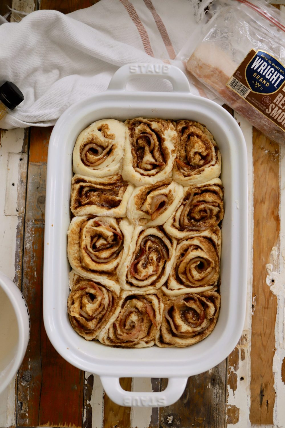 Deliciously Salty Sweet Bacon Cinnamon Rolls with Bourbon Glaze from food and lifestyle blogger Tabitha Blue of Fresh Mommy Blog | Bacon Cinnamon Rolls by popular Florida lifestyle blog, Fresh Mommy Blog: image of bacon cinnamon rolls in a white ceramic baking dish.