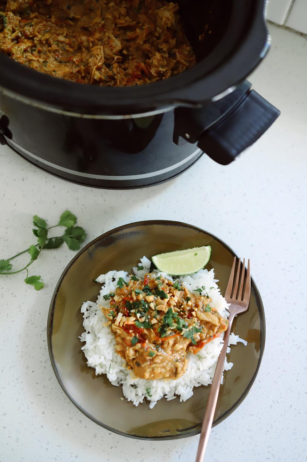 Slow Cooker Thai Chicken with Peanut Sauce recipe from Tabitha Blue of Fresh Mommy Blog   Slow Cooker Thai Chicken by popular Florida lifestyle blog, Fresh Mommy Blog: image of slow cooker Thai chicken with peanut sauce over white rice on a brown ceramic plate with a rose gold fork.