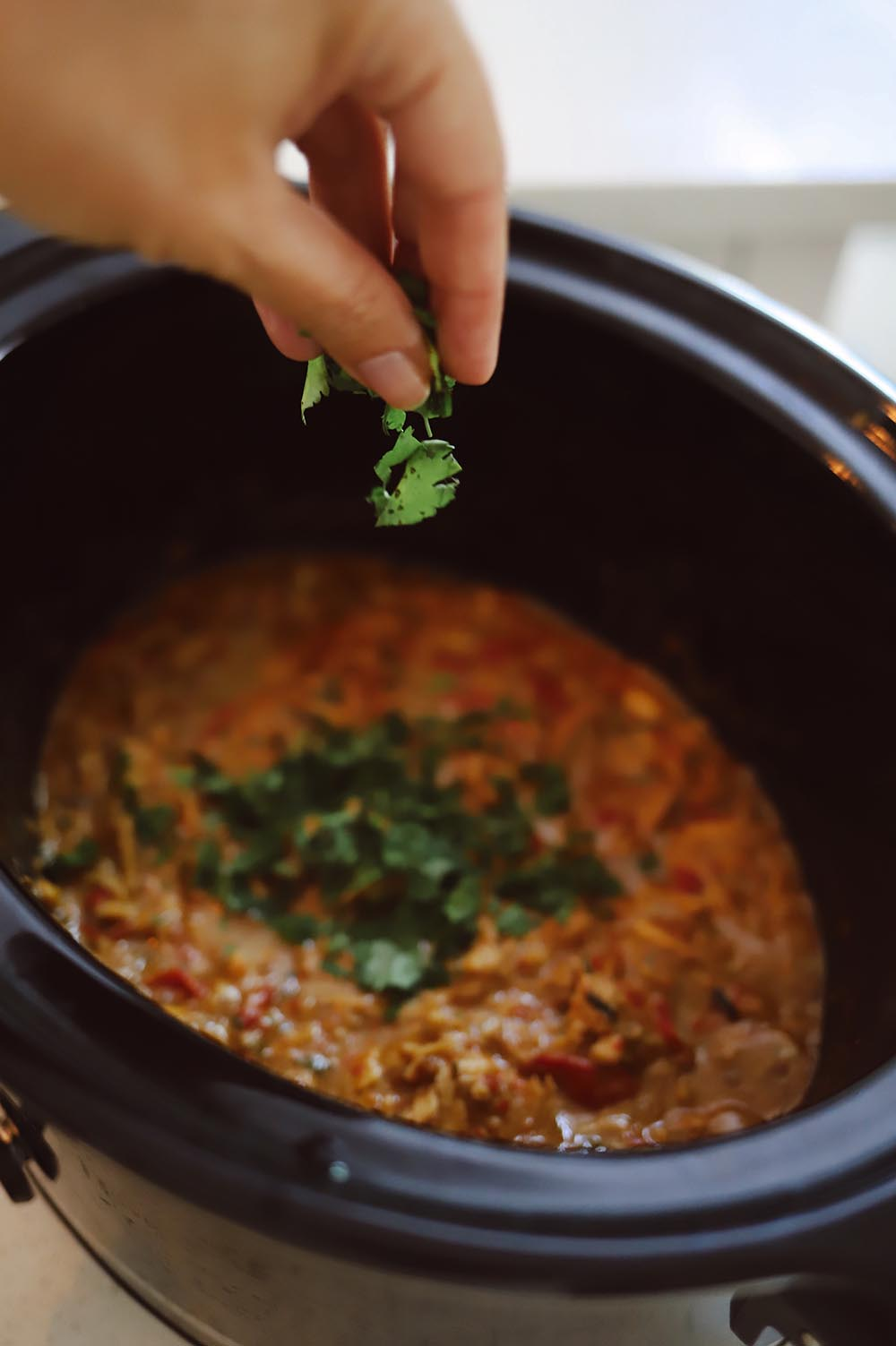 Slow Cooker Thai Chicken with Peanut Sauce recipe from Tabitha Blue of Fresh Mommy Blog   Slow Cooker Thai Chicken by popular Florida lifestyle blog, Fresh Mommy Blog: image of a woman putting chopped cilantro into a slow cooker.