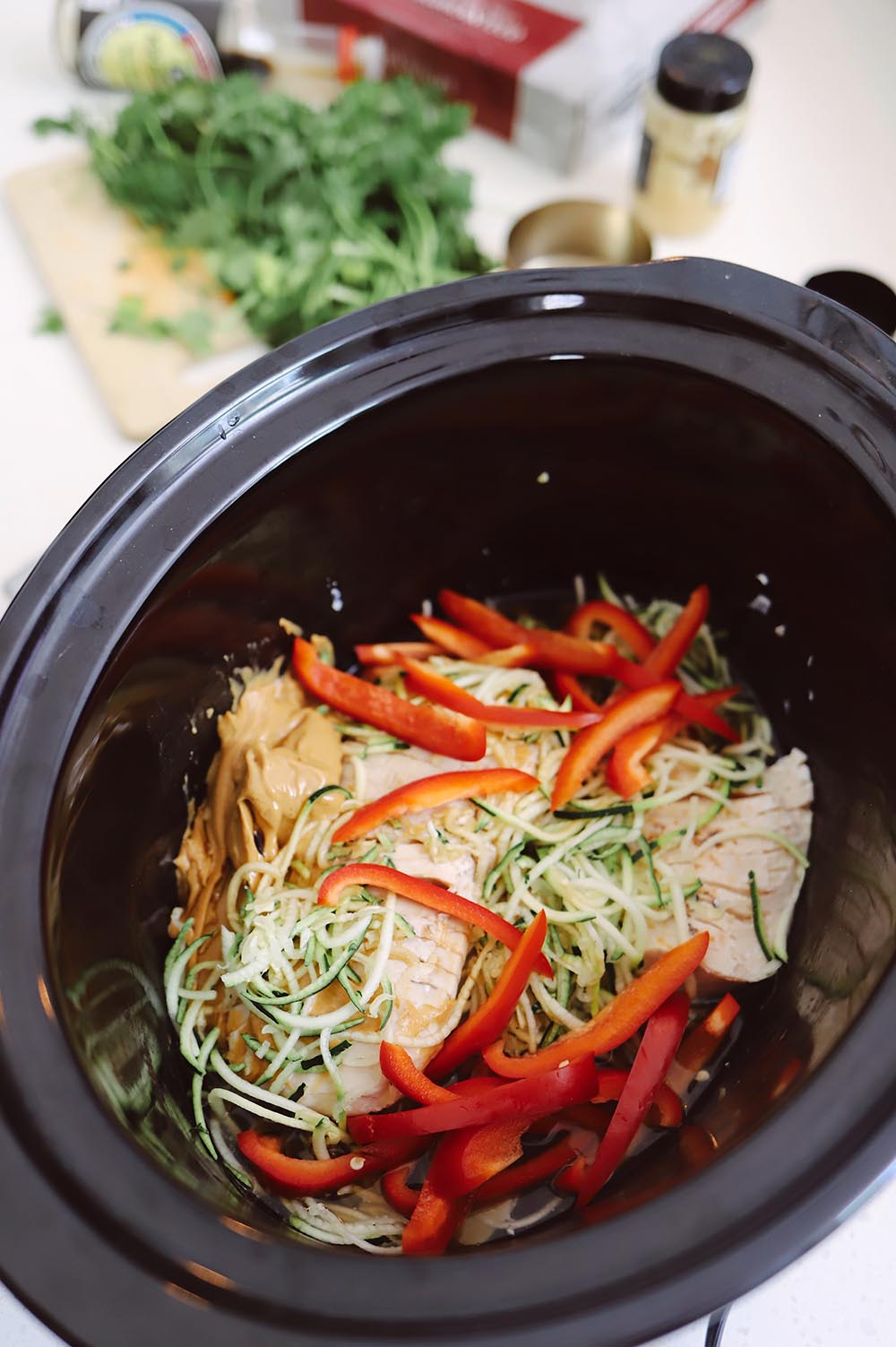 Slow Cooker Thai Chicken with Peanut Sauce recipe from Tabitha Blue of Fresh Mommy Blog   Slow Cooker Thai Chicken by popular Florida lifestyle blog, Fresh Mommy Blog: image of chicken, peanut butter, red peppers, and zucchini in a crockpot.