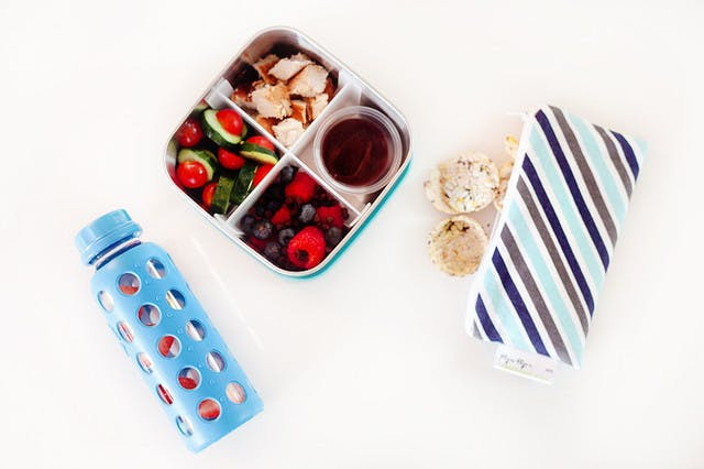 Five lunchbox lunchable hacks that are easy to put together, packed full of nutrients to fuel their school day and can absolutely be made ahead of time so the morning of is still as easy as reaching in the refrigerator. | Healthy Lunchables by popular Florida lifestyle blog, Fresh Mommy Blog: image of a metal bento box filled with cucumbers, cherry tomatoes, blueberries, raspberries, and chopped chicken.